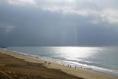 Beach under the bright sun on the ocean. Beautiful rain clouds and glare on the surface of the water. Waves of the surf stock image