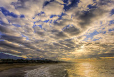 On the beach, under the clouds Stock Images