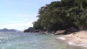 Beach on an uninhabited island. Against a cliff and trees stock footage