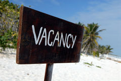Beach vacancy. A brown board with the word vacancy on it, a paradise beach with palm trees in the background Royalty Free Stock Photography