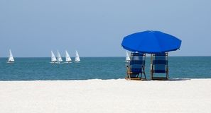 Beach vacation. Beach umbrella and chairs to watch the passing sailboats Royalty Free Stock Photos