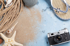 Beach vacation background. Camera, starfish and flip-flops on stone backdrop with sand. Top view with copy space Royalty Free Stock Photo