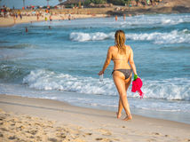 Beach vacation. Beautiful woman in bikini enjoying perfect sunny day walking on the Ipanema beach, Rio de Janeiro Royalty Free Stock Photography