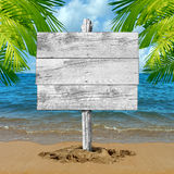 Beach Vacation Blank Sign. Beach wood sign and tropical vacation blank billboard background as an ocean wave on sand with palm tree leaves as a travel symbol for Stock Photo