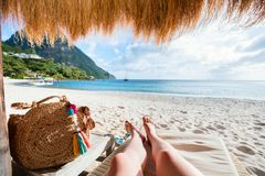 Beach vacation. Close up of young woman legs relaxing at tropical sandy beach stock image