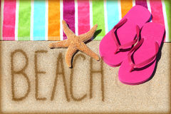 Beach vacation concept - word written in sand. Beach vacation concept - word written on golden sand with a starfish, pink flip flops and towel conceptual of a Royalty Free Stock Images