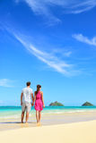 Beach vacation couple relaxing on summer holidays. Young people standing from behind holding hands looking at the ocean on Lanikai beach, Oahu, Hawaii, USA Royalty Free Stock Photo