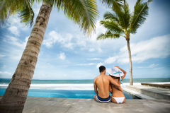 Beach vacation couple on summer holidays. Young happy Asian couple sitting on the rim of the swimming pool with the sea in the background Stock Photos