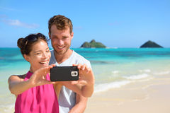 Beach vacation couple taking selfie on smartphone Stock Image