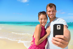 Beach vacation couple taking selfie on smartphone Stock Images