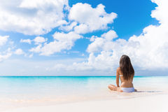 Beach vacation dream woman enjoying summer holiday. On dreamy perfect ocean tropical destination. Person sitting from the back alone on deserted white sand stock photography