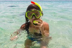 Beach vacation fun woman wearing a snorkel scuba mask making a goofy face while swimming in ocean water. Closeup. Portrait of Asian girl on her travel holidays royalty free stock photo