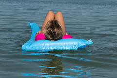 Beach vacation girl relaxing in blue plastic pool air bed Stock Photos