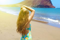 Beach vacation. Hot beautiful woman in swimsuit standing with her arms raised to her head enjoying looking view of beach ocean on. Hot summer day in Tenerife royalty free stock photo