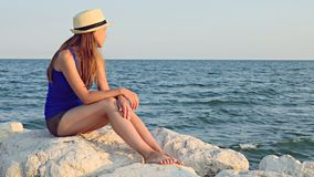 Beach vacation woman relaxing resting on the stony beach looking at sea water. One teenage girl sitting alone on rocks sea beach in the summer evening stock video footage