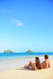 Beach vacations suntan couple relaxing in Hawaii. Beach vacations suntan couple relaxing in Lanikai, Oahu, Hawaii, USA. Vertical crop with blue sky copy space stock photos