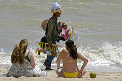Beach vendor and women sunbathers, Brazil. Typical image on the beaches of northeastern Brazil, beach vendors who sell hats, caps and sunscreen. These products Royalty Free Stock Images