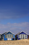 Beach View. A low angled shot of a row of blue wooden beach huts set on a portrait format with room for copy above. Located in Christchurch, Dorset Hampshire UK Royalty Free Stock Image