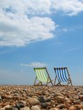 Beach View. Subject: view of two traditional deck beach chairs , alone on a quiet, clean, sunny beach Stock Photos