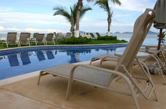 Beach view closeup. Some chairs on a beach front pool waiting for you to sit on them Stock Photography