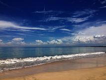 Beach view. Kuta beach, in Bali Indonesia with sand, waves and cloudy blue sky Stock Photo