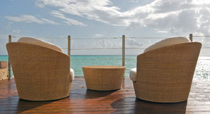 Beach View at Luxury Resort. Beach view from the balcony of a luxury hotel in Playa del Carmen, Mexico overlooking the calm blue Caribbean Sea. Wicker chairs and Royalty Free Stock Images