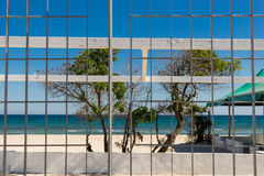 Beach view through a metal railing. Close up view of beach Stock Images