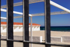 Beach view through a metal railing. Close up view of beach Royalty Free Stock Photography