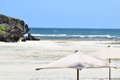 Beach view with rocks and parasol Stock Photography