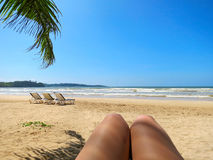 Beach view in selfie style with legs and palm leaf Royalty Free Stock Image