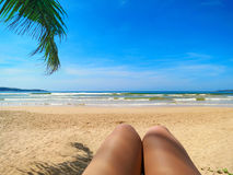 Beach view in selfie style with legs and palm leaf. Beach view in selfie style with woman legs and palm leaf royalty free stock photos