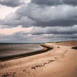 Beach view with storm clouds. Beach at sunset in Prince Edward Island, Canada with dark cloudy sky, square format stock photo