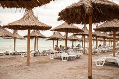 Beach view with tourists tanning and umbrellas Stock Image