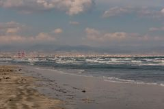Beach view with white topped waves at Ladys Mile in Limassol. Ladys Mile, Limassol, Cyprus, November 8, 2018: Beach view looking toward the town of Limassol on a royalty free stock photography