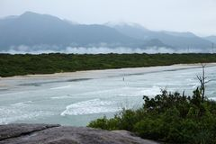Beach views of the mainland with waves, forest, clouds and mountains. stock photography