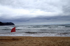 Beach of Villaviciosa in Spain. Landscape of atlantic sand beach of Villaviciosa in Spain with red flag Royalty Free Stock Photography