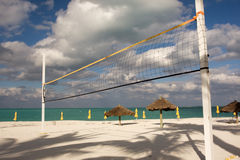 Beach volley ball. Net with sun shades and turquoise sea Royalty Free Stock Photo