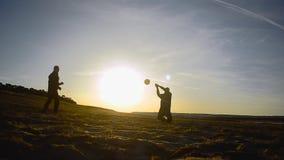 Beach volley sulla sabbia sulla sera della molla, uomini di addestramento nella pallavolo sulla spiaggia un giorno soleggiato archivi video