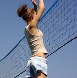 Beach Volleyball. Young girl hitting the ball over the net stock photography