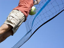 Beach Volleyball. Young man hitting the ball over the net stock images