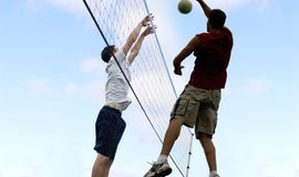 Beach Volleyball. Young men hitting the ball over the net stock photos