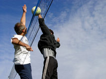Beach Volleyball. Young men hitting the ball over the net Royalty Free Stock Photography