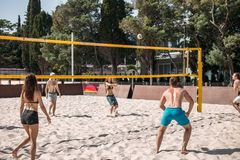 Group young caucasian friends playing volleyball on beach on summer vacation stock photo