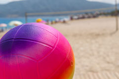 Beach volleyball ball in the foreground on the sand beach Royalty Free Stock Photos