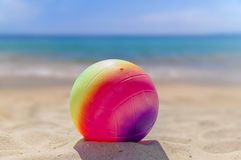 Beach volleyball ball in the foreground on the sand beach Royalty Free Stock Photo