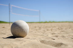 Beach volleyball court on sunny day. Image of volleyball sitting on sand with court in background Royalty Free Stock Image