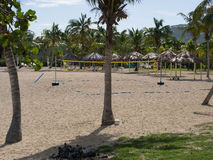 Beach with Volleyball Court and Tiki Shelters and Palm Trees Stock Image