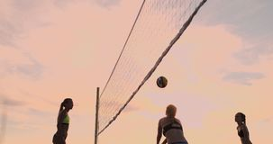 Beach volleyball match girls hit the ball in slow motion at sunset on the sand. Beach volleyball match girls hit the ball in slow motion at sunset on the sand stock footage