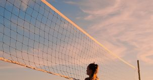 Beach volleyball match girls hit the ball in slow motion at sunset on the sand. Beach volleyball match girls hit the ball in slow motion at sunset on the sand stock video footage
