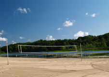 Beach Volleyball Net. Volleyball net stands alone on a raked beach by a small lake Stock Images